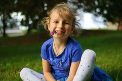 有浅褐色的头发的可爱的卷曲女孩坐草 她拿着在她的嘴的一朵紫色三叶草花 婴孩 免版税库存图片