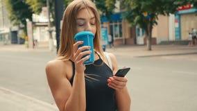 有浅褐色的头发的可爱的年轻女人在市中心使用智能手机并且喝咖啡 股票视频