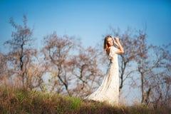 有浅褐色的头发的美丽的苗条女孩在自然,干燥树,绿草,蓝天背景的一件长的轻的礼服  免版税库存图片