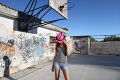 有浅顶软呢帽帽子的少年在有街道画的操场 免版税库存图片