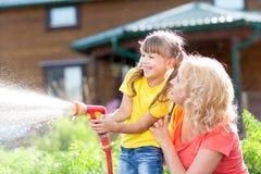 有浇灌在草坪的母亲的小花匠女孩 免版税库存照片