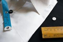 有测量的磁带、木标度和按钮的丝毫衬衣 免版税库存图片
