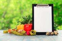 有测量的磁带和各种各样的菜的剪贴板在木t 免版税图库摄影