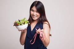 有测量的磁带和沙拉的健康亚裔妇女 库存图片