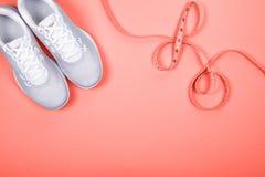 有测量的磁带的白色运动鞋在蓝色背景 免版税图库摄影