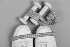 有测量的磁带的运动鞋在绿色背景 体育鞋子和设备健康形状的 健身连续概念 免版税库存图片