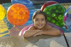 有浮动圆环和海滩球的女孩在游泳池 图库摄影
