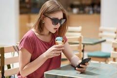 有浮动的发型的严肃的相当年轻欧洲女性,在互联网佩带树荫,下载照片,使用现代巧妙的电话fo 库存图片