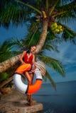 有浮游物管的美丽的女孩在海滩 免版税库存图片