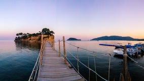 有浮雕的贝壳海岛,有木吊桥的扎金索斯州在日落 免版税库存图片