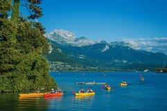 有海岛、植被、皮船、峰顶和蓝天的Annecy湖,在阿讷西, 库存图片