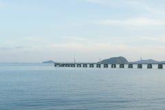 有海岛和天空背景的长的具体跳船 图库摄影