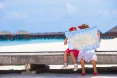 有海岛地图的可爱的小女孩海滩的 免版税库存图片