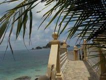 有海洋的美丽的石台阶在背景中,在海滩Pulau Kapas海岛 免版税库存图片