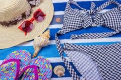 有海滩辅助部件的泳装在蓝色背景 太阳镜顶视图贝壳短缺触发器泳装 免版税库存照片