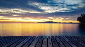 有海的木在日出的码头和山 免版税库存照片