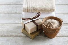 有海盐、两块软的手工制造s毛巾和酒吧的陶瓷罐  免版税库存照片