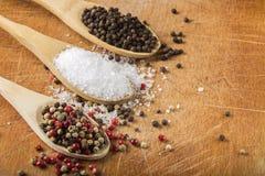 有海盐和干胡椒的木匙子在木头 免版税库存图片