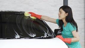 有海绵的妇女洗涤的挡风玻璃在洗车 股票视频