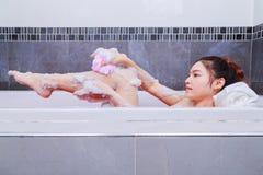 有海绵的妇女洗涤的腿在浴缸在卫生间里 库存图片