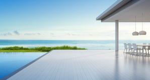 有海视图游泳池的豪华海滨别墅和在现代设计,室外用餐的空的大阳台在大家庭的别墅 免版税库存图片