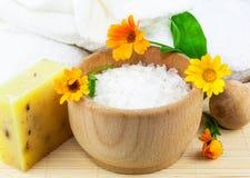 有海运盐、肥皂、毛巾和万寿菊的木碗 库存图片