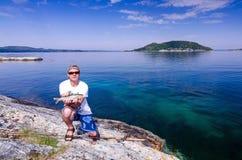 有海鳟的钓鱼者在挪威 免版税库存图片