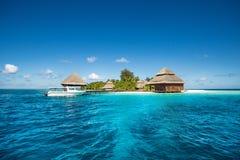 有海滩别墅和速度小船的小热带海岛 库存图片