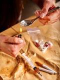 有海洛因匙子和打火机的女孩上瘾者 库存照片