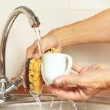 有海绵的手洗涤咖啡杯在自来水下在厨房里 免版税库存图片