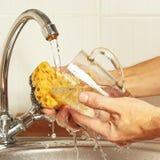 有海绵的手洗涤玻璃在自来水下在厨房里 免版税库存照片