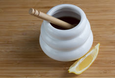 有浸染工和柠檬切片的白色蜂蜜罐 库存图片