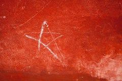 有涂灰泥和星的红色混凝土墙 免版税图库摄影