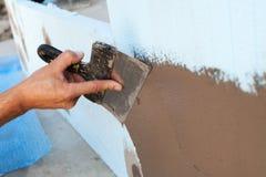 有涂灰泥墙壁的修平刀的人手 免版税库存照片