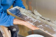 有涂灰泥墙壁的修平刀的人手 图库摄影