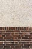 有涂灰泥的上面的外部墙壁在红色炼砖底部 免版税库存照片