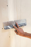 有涂灰泥石膏板的修平刀的人手 免版税库存照片