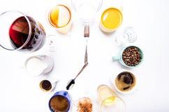 有液体的杯喜欢咖啡,牛奶,酒,酒精,在圈子堆积的汁液 时钟包括十二个杯子 时间 闹钟 免版税库存照片