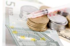 有液体的注射器在货币 免版税图库摄影