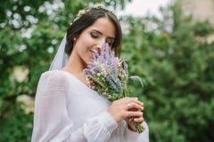 有淡紫色花束的新娘浅黑肤色的男人 免版税库存图片