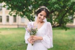 有淡紫色花束的新娘浅黑肤色的男人 免版税库存照片