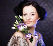 有淡紫色花的美丽的深色的妇女 免版税库存图片
