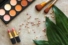 有淡色化妆用品的妇女书桌在灰色石背景顶视图样式设置了 免版税库存照片