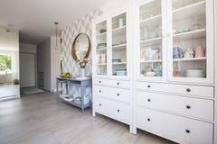 有淡色盘和蓝色嵌墙桌子的白色厨房碗柜 库存照片
