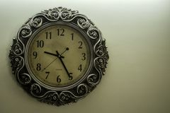 有淡黄色后面地面陈列时间09:25时的古老设计师壁钟和在右边的自由spac 库存照片