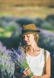 有淡紫色花束的女孩佩带的草帽开花 免版税库存照片