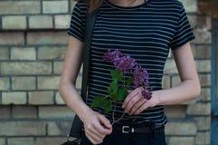 有淡紫色花的未知的女孩 免版税图库摄影