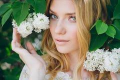 有淡紫色花的白肤金发的妇女在春天 库存照片