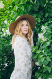 有淡紫色花的白肤金发的妇女在春天 免版税库存照片