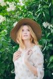 有淡紫色花的白肤金发的妇女在春天 图库摄影